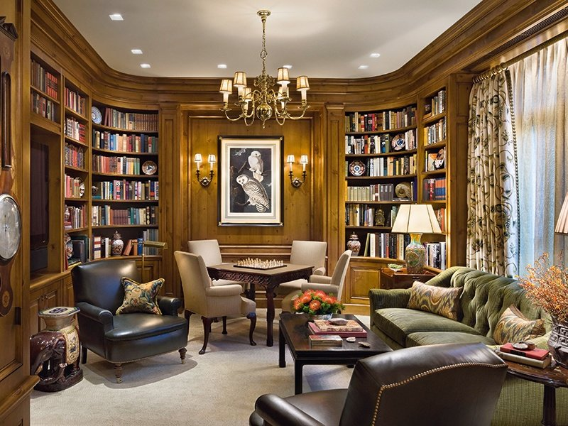 Settle down: Robert AM Stern Architects and Arthur Dunnam used wood paneling to create a cozy, intimate ambience at this den in a Chicago home. Incorporating the owners' ornaments and books adds individual character to the space.
