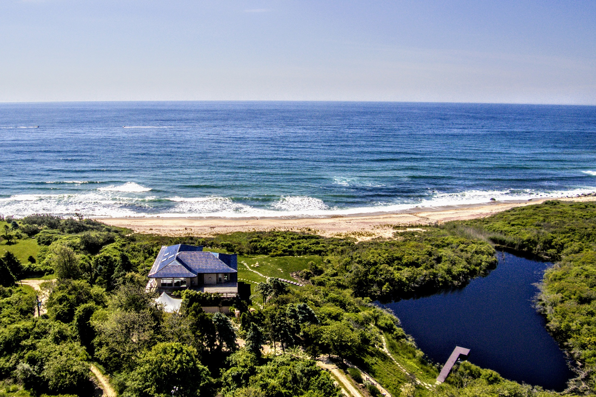 An aerial vantage underscores the expansiveness of the home's private beach.