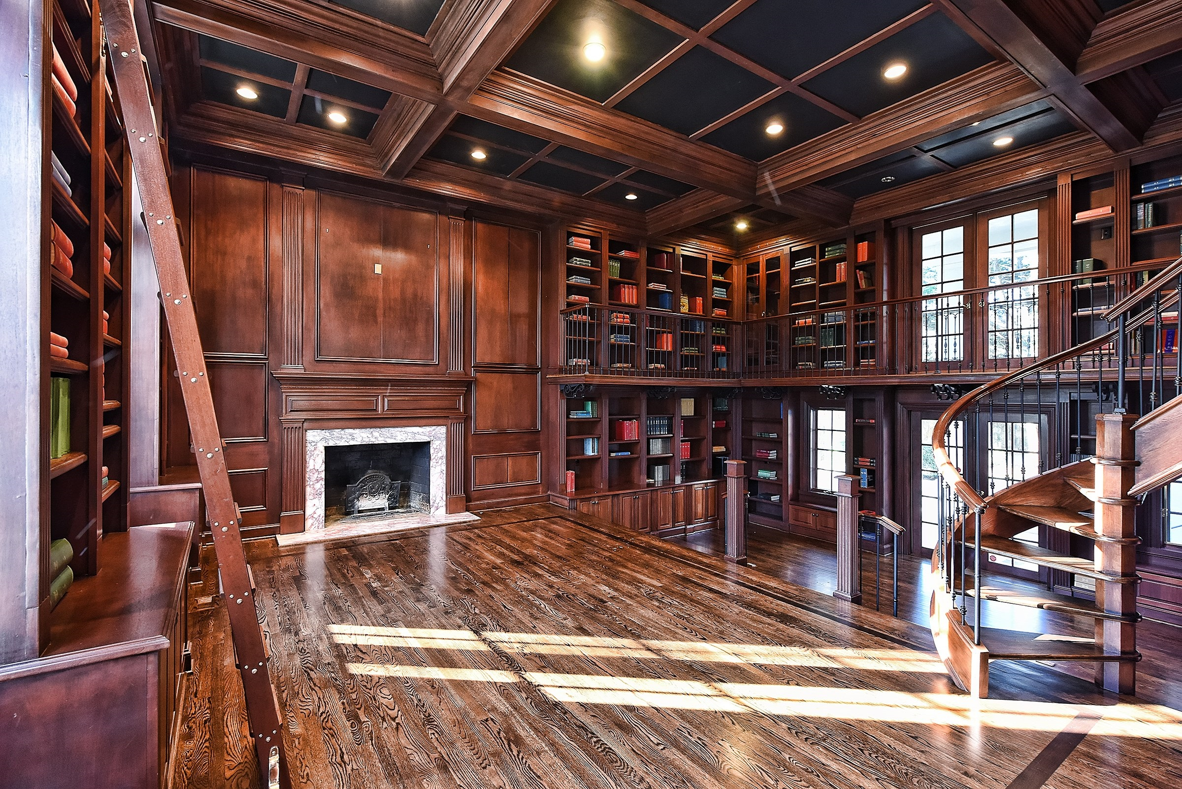 The mahogany walls, stairs, shelving, and ceiling in this grand library bring to mind comfort-rich reading rooms of old.