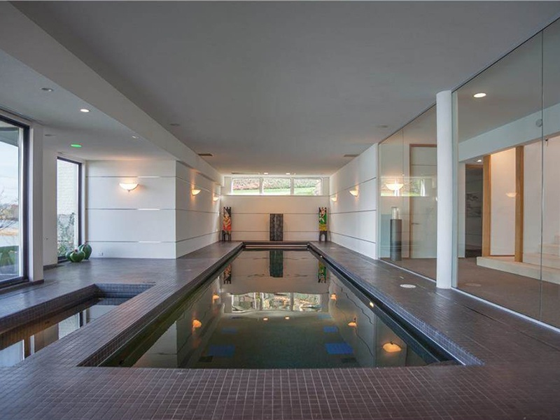 A glass and tile indoor pool on the lower level of the property also looks out toward the lake. Photograph: Hall & Hunter Realtors