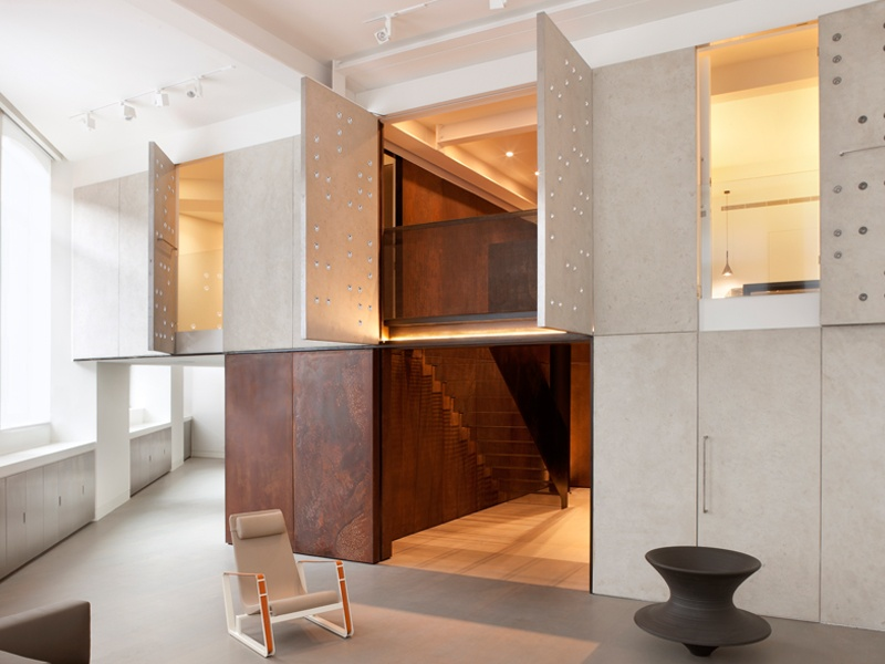 Set in a converted Victorian Post Office, this dramatic London apartment—Project Elizabeth—features striking contemporary materials such as pre-cast concrete panels and chemically weathered steel. In the main reception room, panels are studded with bespoke acrylic lenses, which distort and amplify light.