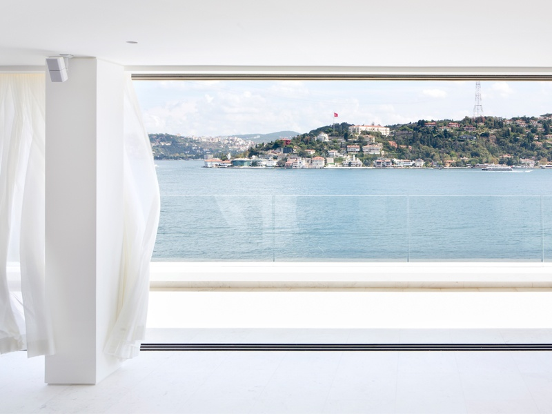 The modern, open-plan living space at Project Esra is encased in minimalist frameless windows, revealing the sweeping views of the Bosphorus.