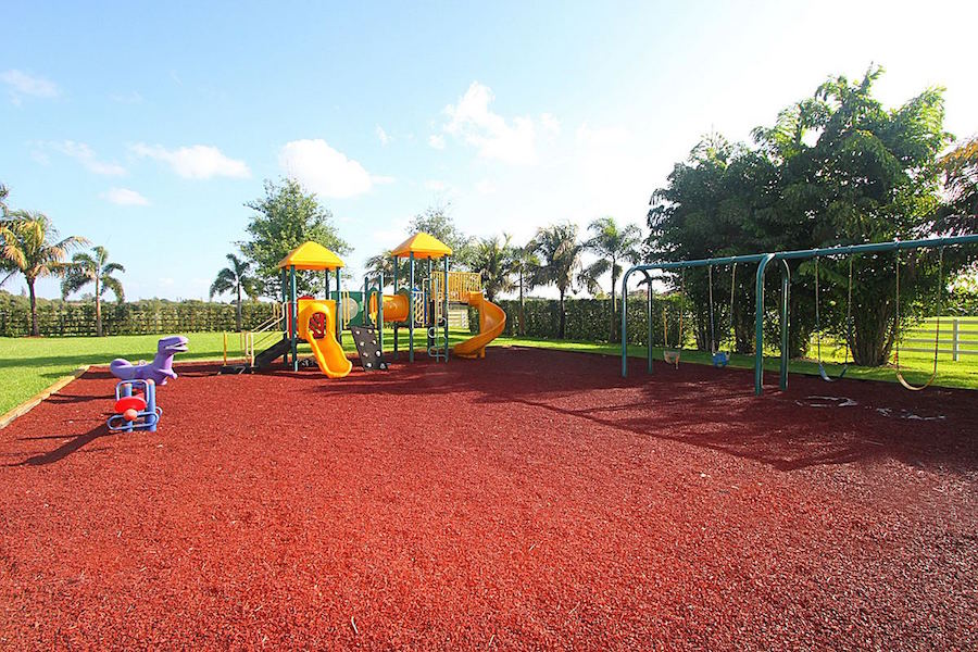 A full sized playground surrounded by palm trees has a swing set, a jungle gym, and plenty of space to run around in the Florida sunshine.