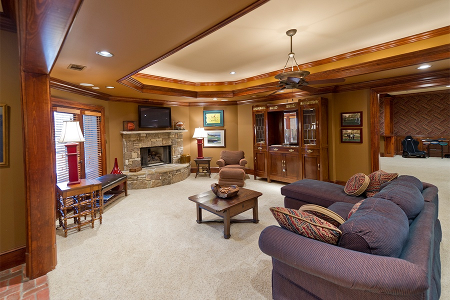 A warm and inviting family room has a stone fireplace and a flat screen TV, cozy carpeting, and carved wood details.