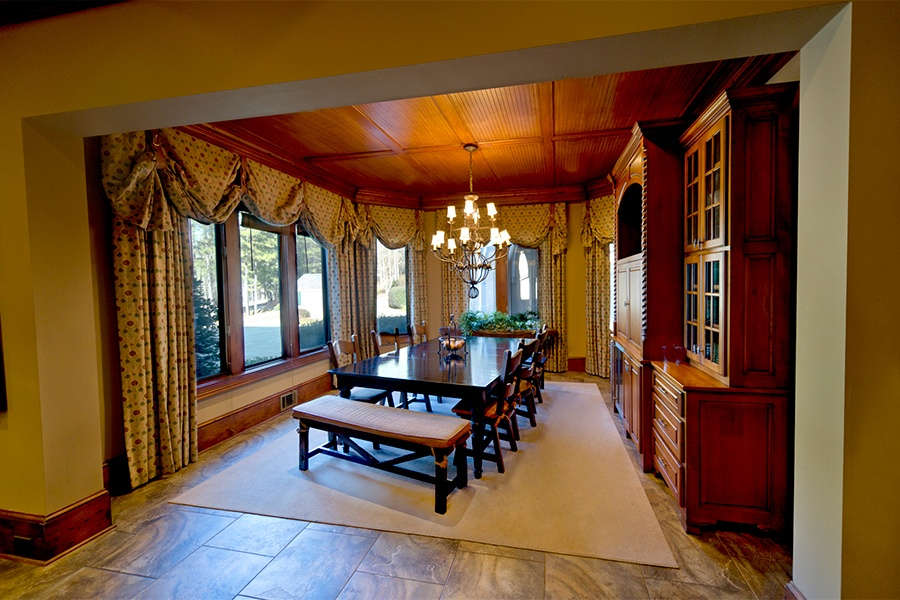 The estate's formal dining room has a charming beadboard ceiling and wraparound windows that provide scenic views.