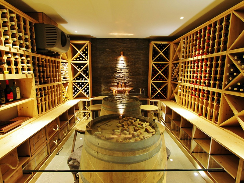 """This wine cellar, built into a home refurbished by BTL Property, is complete with a stunning glass table, made using wine barrels as """"legs"""", to create an area for tastings."""