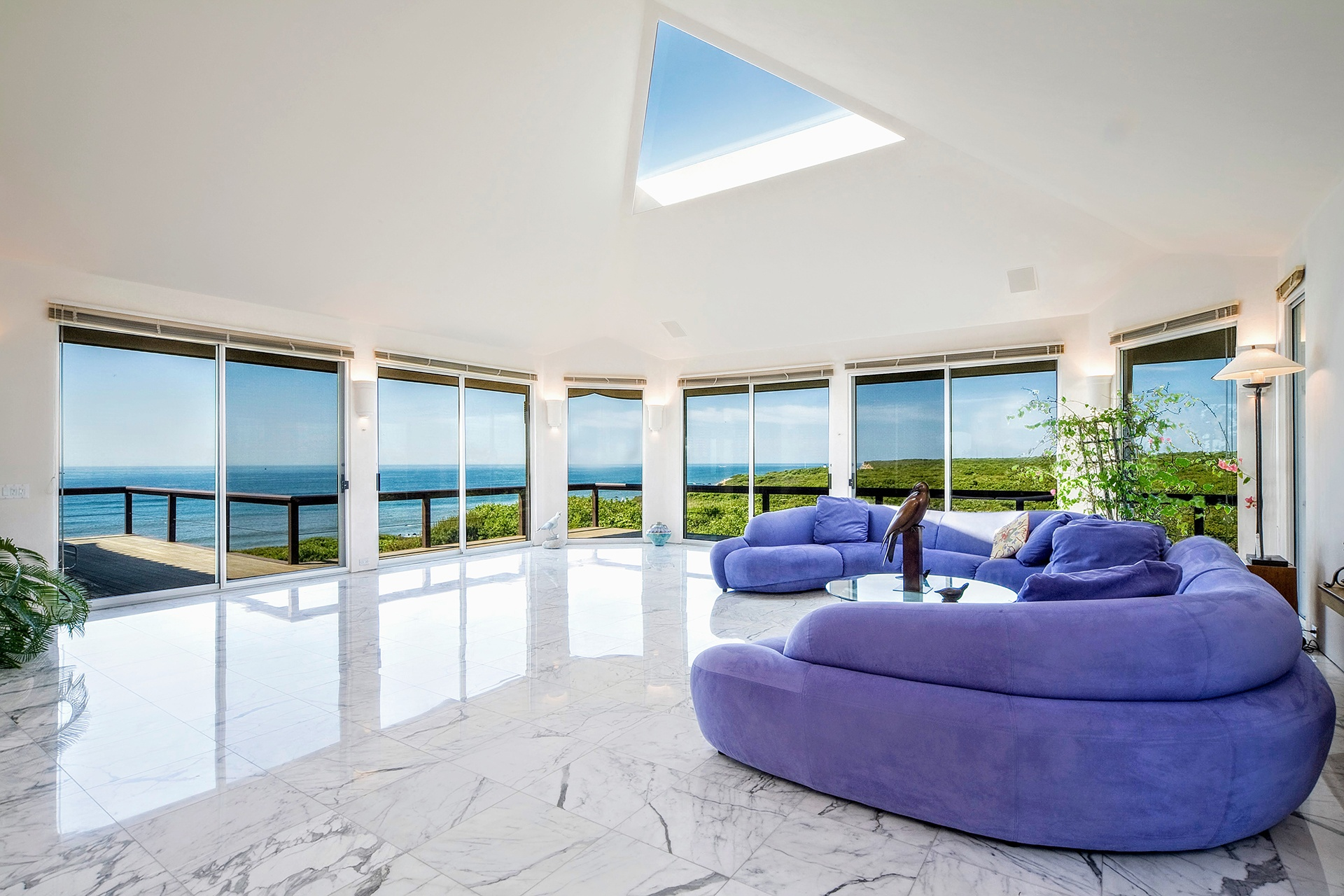 The white-marble living room is a striking contrast to the cobalt-blue sea and emerald-green bluffs.