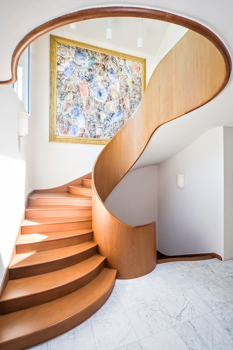 The sculpted wood staircase is among the home's many artisanal touches.