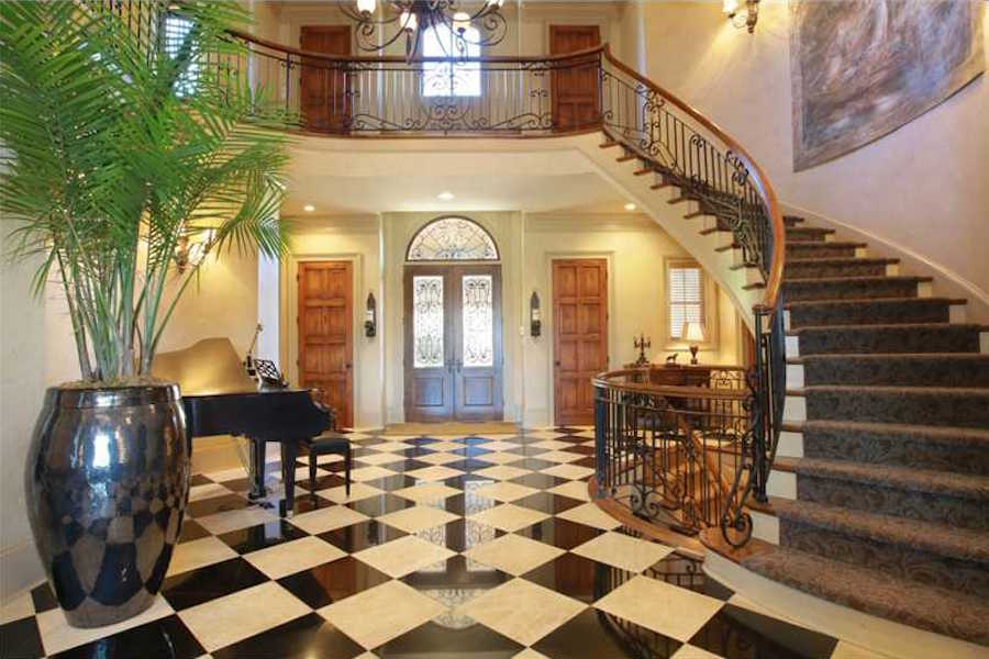 A grand curved staircase with a wrought-iron banister is the centerpiece of the entryway, which has a bold and graphic black and white marble floor.