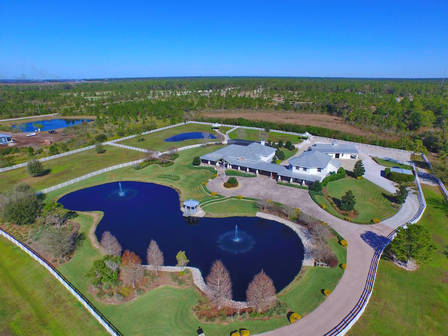 Located on eight lush acres, this private and secluded 5-bedroom estate in Bradenton, Florida boasts a main residence of over 7,000 square feet plus a custom-built barn with state-of-the-art technology as well as four stalls, a tack room, and a full bath.