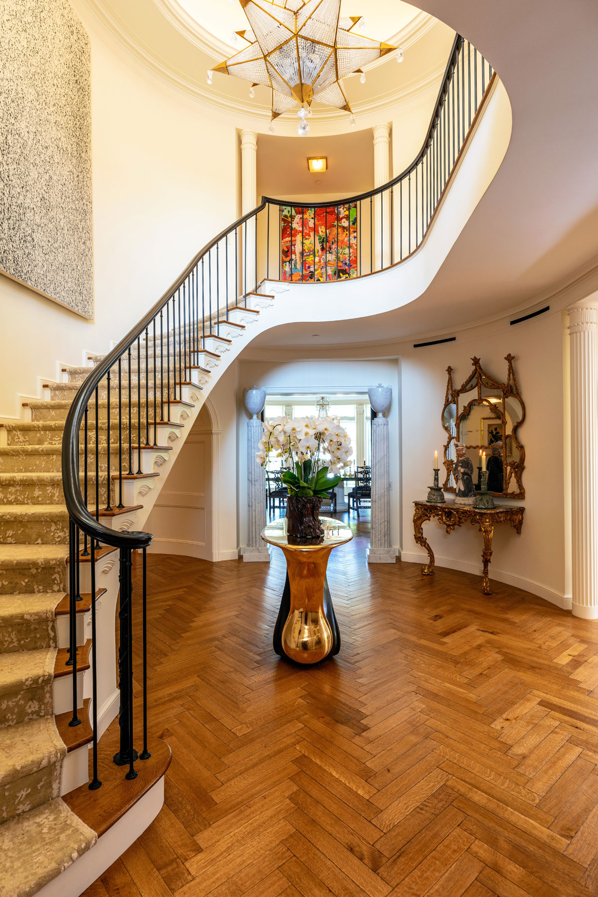 A graceful, curved staircase is the centerpiece of the estate's entry foyer.