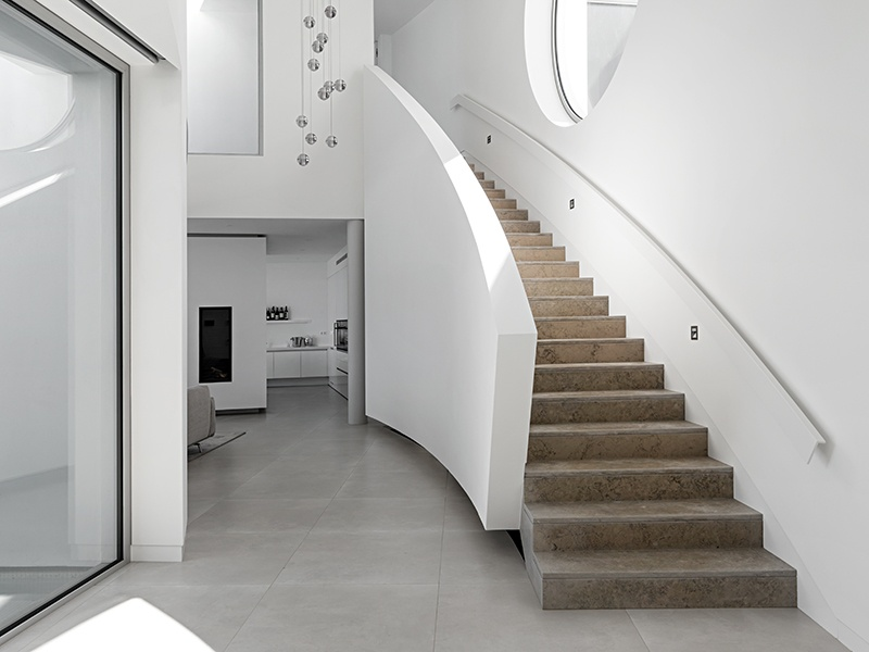 Further highlights of Elliptical House in Luz, Portugal, include minimalist interiors and a marble staircase that follows the curve of the building.