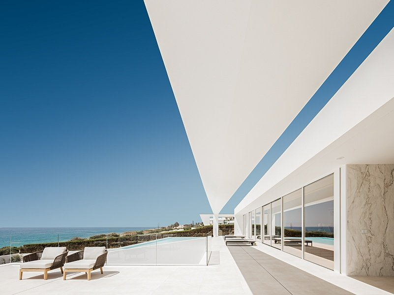 Villa Escarpa's poolside area is an oasis of white overlooking the Luz coastline in Portugal.