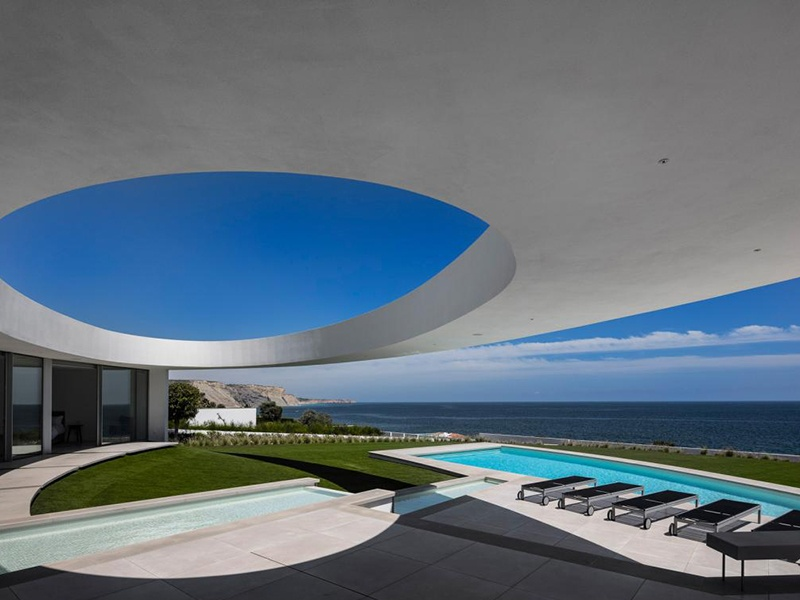 A wide floating oval subtly determines the boundaries of the central patio of Elliptical House in Luz, Portugal.