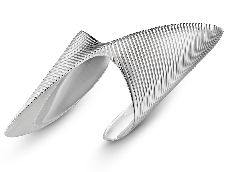 The defining piece of Zaha Hadid's Lamellae collection for Georg Jensen, the Twisted Bangle vividly captures the fluidity that is central to her architecture. Engineered and refined using 3D technology and processes, its form is inherently elegant and modern. The collection also includes a range of sterling silver bangles and rings, as well as gold and black rhodium finishes.