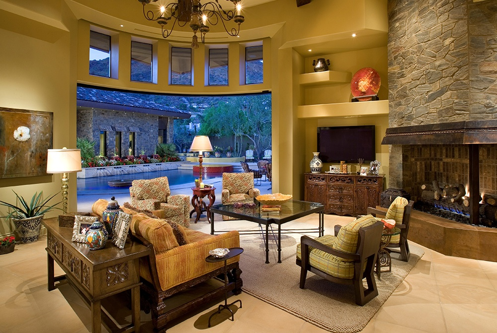 The great room of this hacienda-style home in the Desert Southwest is warmed by a stunning two-story stone fireplace.