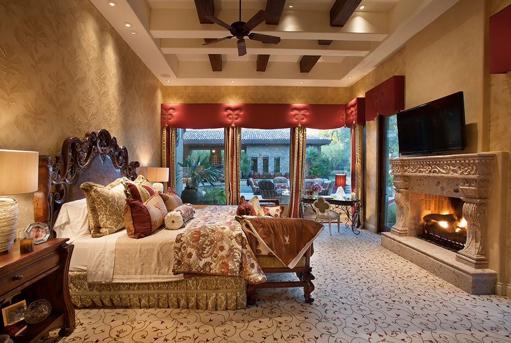 This decorative carved stone fireplace adds to the grandeur of the master suite.