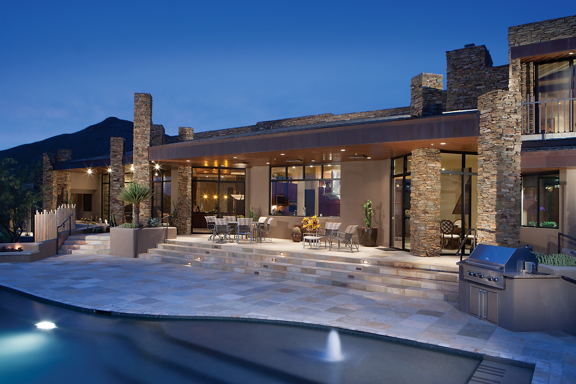 At one with its magnificent setting in the Sonoran Desert, this contemporary retreat features a covered dining terrace with mountain, city light, and sunset views.