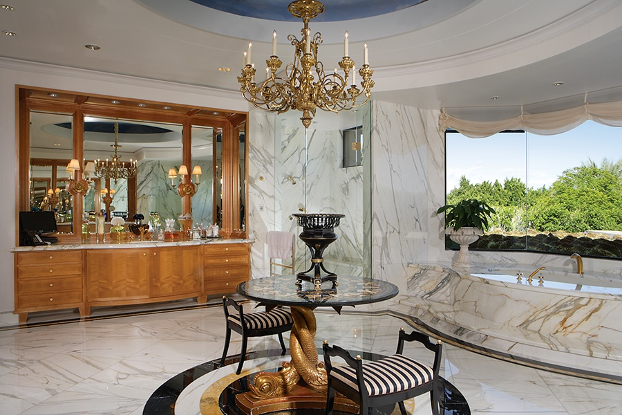 The gilded chandelier, gold-streaked marble, and stunning wood vanity in this bathroom exemplify the level of luxury found throughout this Arizona estate.