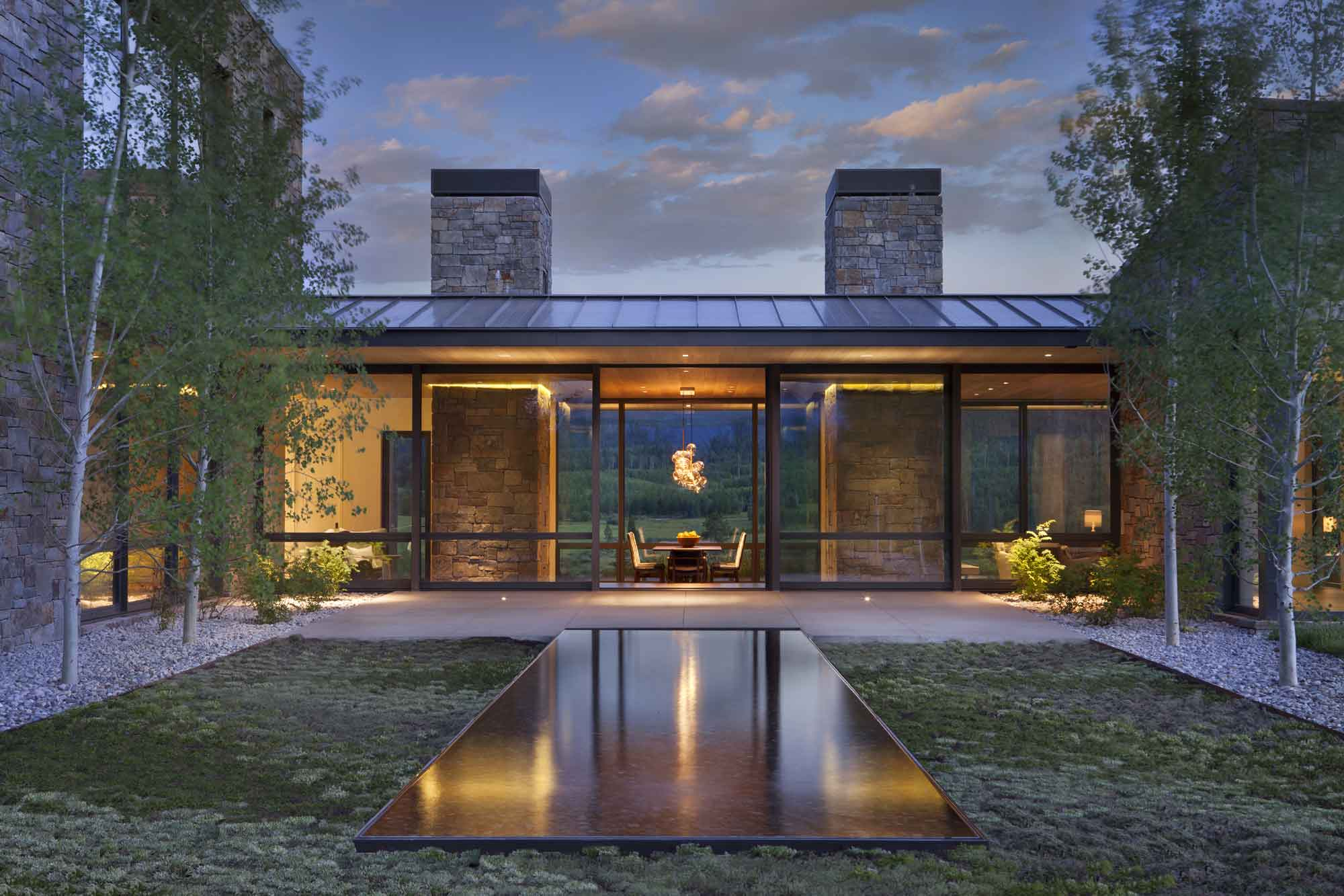 This contemporary residence in Jackson Hole's Crescent H Ranch is enveloped in glass to take advantage of its spectacular setting in the Bridger-Teton National Forest.