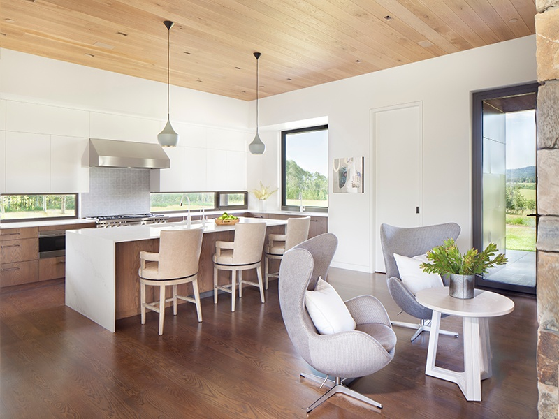 Located at one end of the open layout, the kitchen boasts custom cabinetry, a breakfast bar and relaxed seating area for two. Photograph: Gibeon Photography