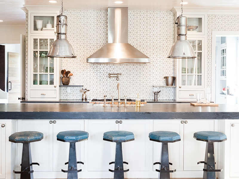 In the kitchen of the Atlanta home, a soapstone-topped island with storage looks out to the living areas and fireplace. Vintage stools are covered in a rusticated teal leather, and vintage factory lights hang over the bar.