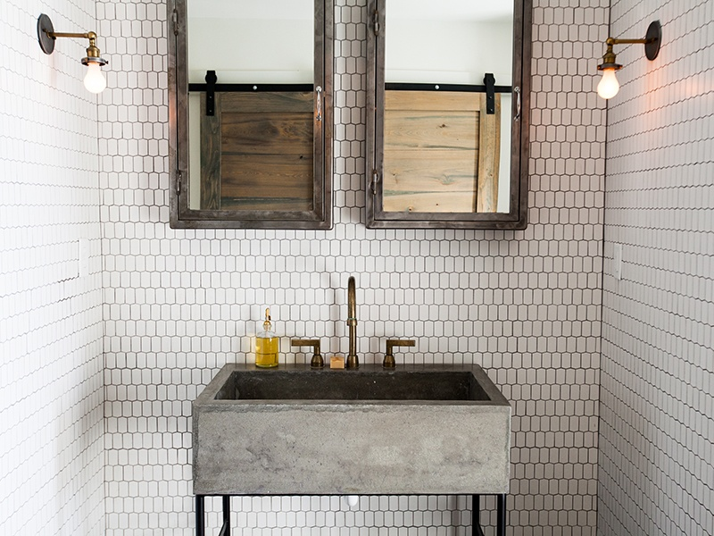 There is an industrial, custom-made concrete sink in the Atlanta home's bathroom, which plays against the more refined Ann Sacks Savoy tile in Hive. The vintage metal wall cabinets are flanked by industrial-style light fixtures.