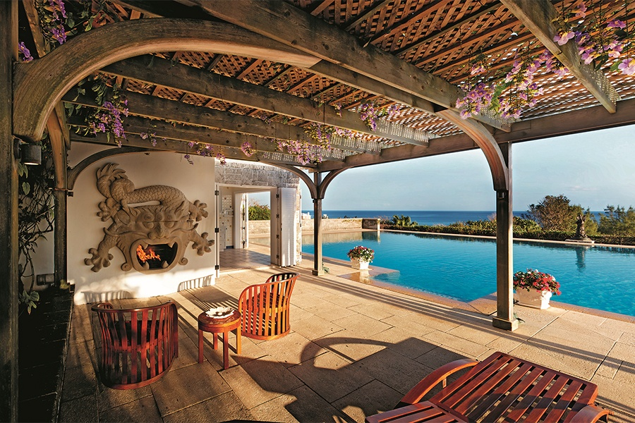 The poolside terrace of this beachside estate features a flower-draped pergola and a stone fireplace in the shape of a five-armed Chinese dragon.
