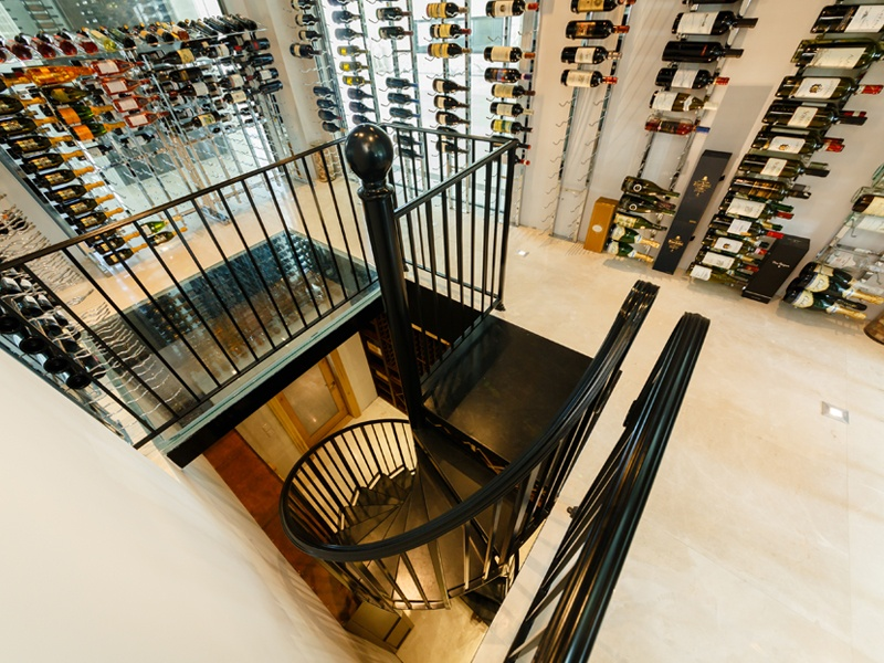 Joe Kline and Curt Dhal of Joseph & Curtis produce one-of-a-kind wine cellars and cabinets, such as this two-story, 4,000-bottle design featuring ultra-modern glass and chrome finishes upstairs and a traditional Tuscan aesthetic on the lower level.