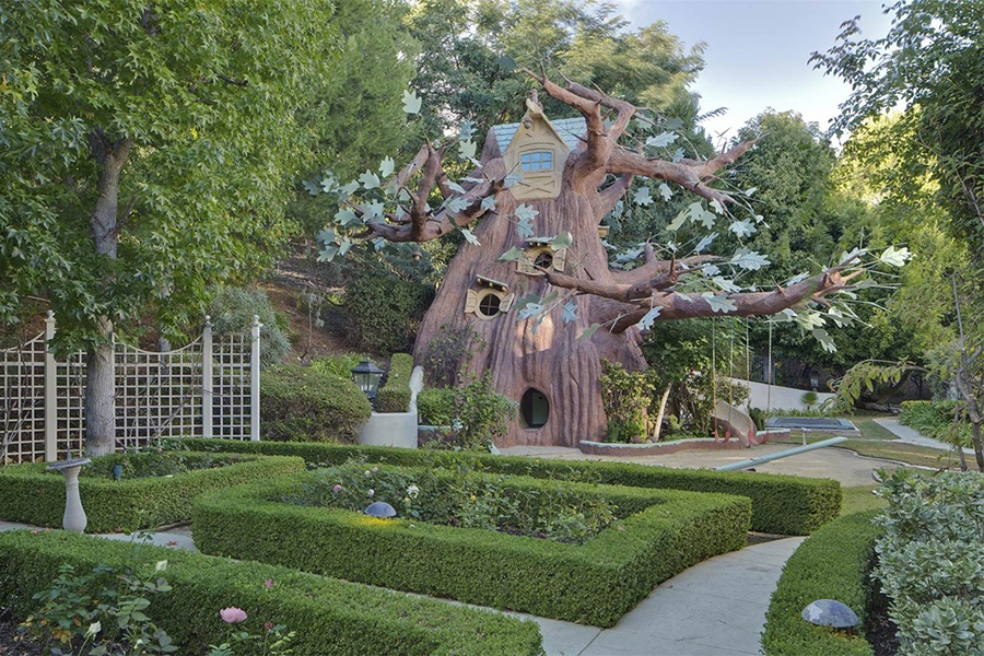 The sprawling grounds of this Beverly Hills estate include a magical multi-story treehouse that could have come from a movie set.