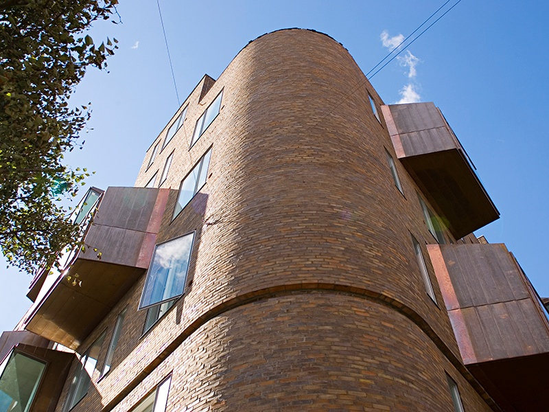 Reddish-brown façades of recycled brick and modernistic bays link Copenhagen's Østerbrogade 105, designed by C.F. Møller, with the local neighborhood. Photograph: C.F. Møller Architects/Torben Eskerod