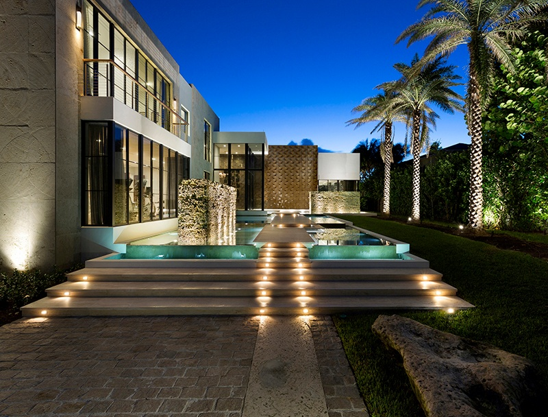 Located in gated grounds, this ocean-to-Intracoastal estate is characterized by top-class finishes including a bespoke Eggersmann kitchen with Macassar ebony cabinets and a butler's pantry. The living room features a wall of windows and opens to a terrace with infinity-edge pool. Elsewhere, a fitness studio, powder rooms, and a luxurious full cabana bath all have opulent finishes.