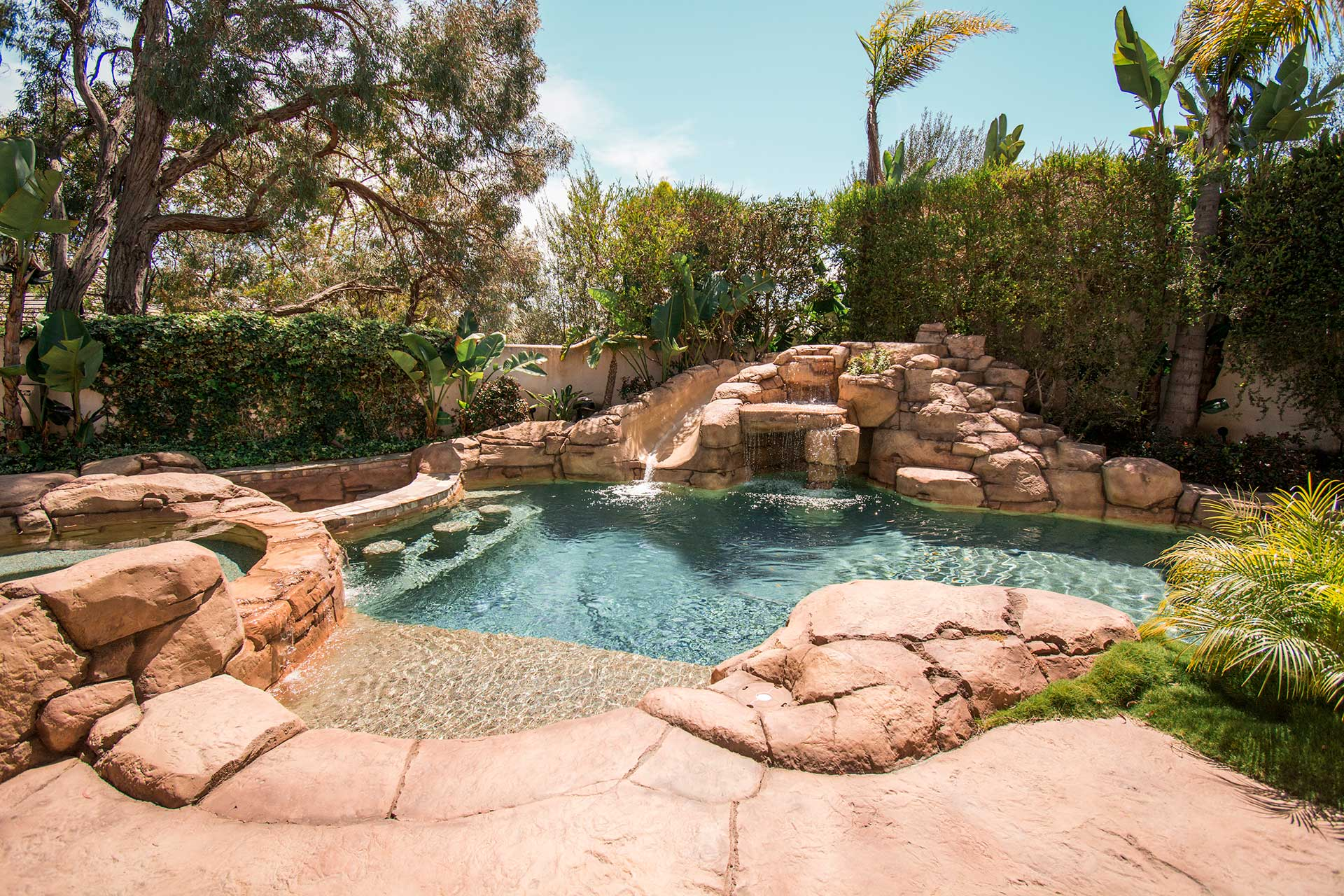 This Southern California home's pool is an entertainer's dream with underwater bar seats, a hot tub, waterslide, and beach entry.