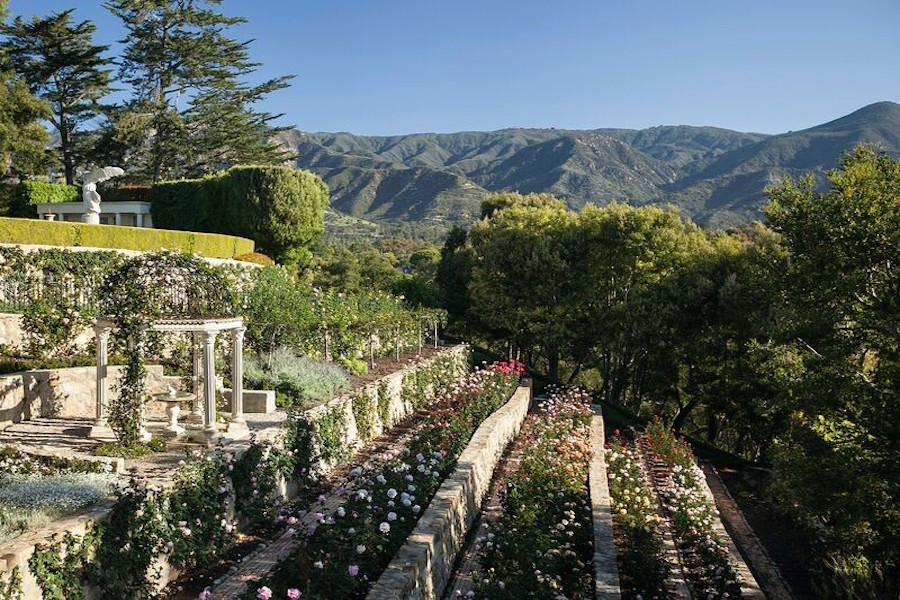 The expansive formal gardens of this manorial estate above the California coast are bathed in sunlight.