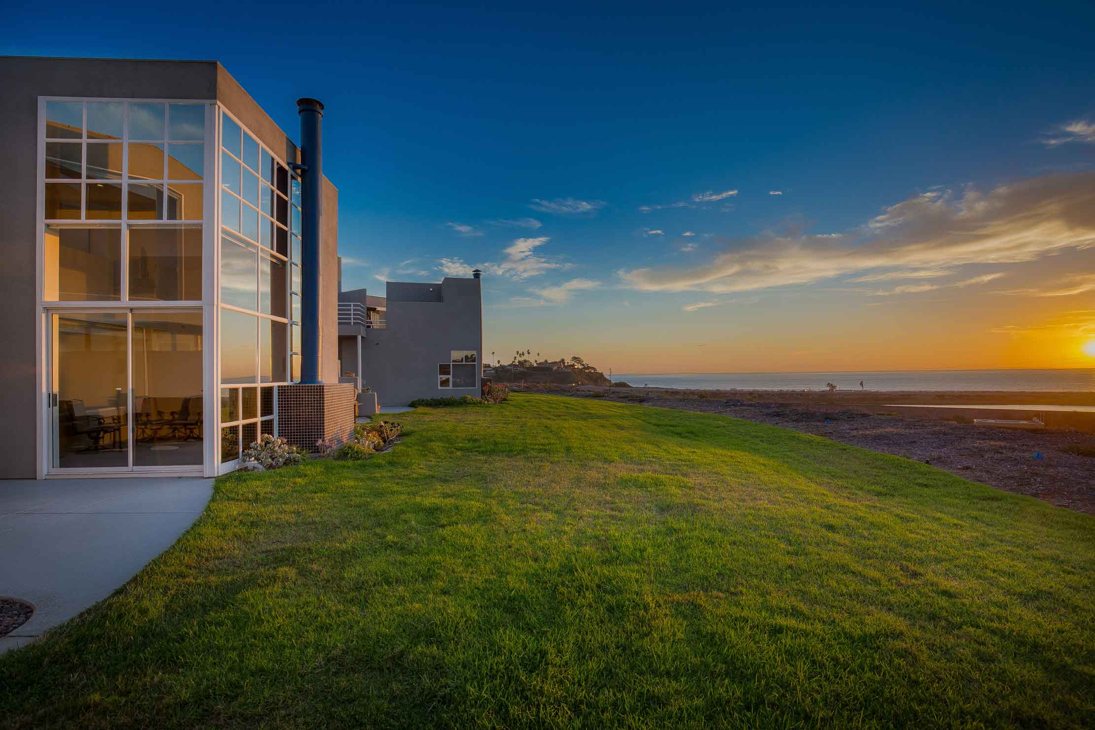 This contemporary condominium on the California coast, just north of San Diego, has a facade of glass that frames the majestic backdrop of Solana Beach and the Pacific Ocean.