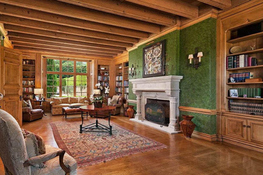A wood-lined library combined with a sitting room features a grand fireplace and French doors that open onto a pleasant terrace.