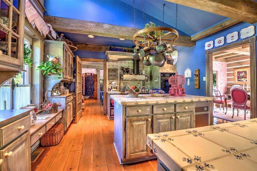 The kitchen's French ceramic tiled counters, an antique-style cook stove, rustic wagon-wheel pot rack, beamed ceilings, pine floors, and country wood cabinets give it the feel of a storybook cottage.