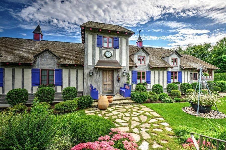 This Tudor-style half-timbered home has all the charm of a fairytale, with its sweet stone walkway, bright blue shutters, shingle roof, and whimsical clock tower entrance.