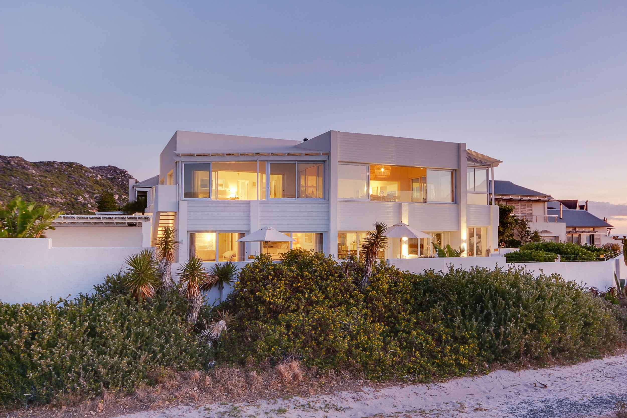 This contemporary retreat on South Africa's Western Cape has an unrivaled beachfront location and plenty of spaces to entertain guests while watching the sunset over Table Mountain and the Atlantic Ocean.