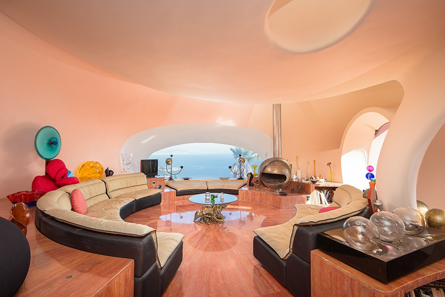 The interior living spaces are custom fitted with built-in round banquettes and furniture with curved edges.