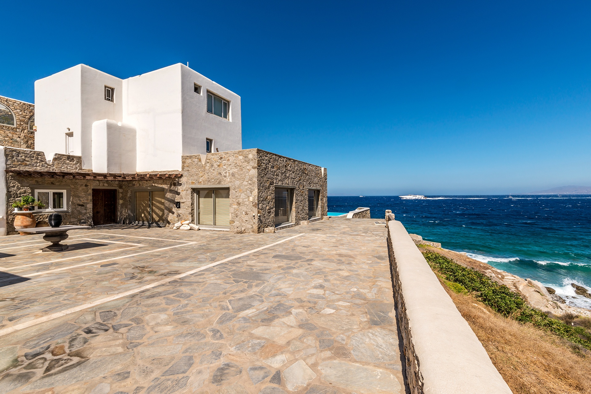 Outside, a vast sunny terrace leads down to the secluded cove and beach.