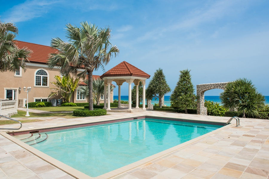 The terrace of this elegant abode overlooks the turquoise waters of the Caribbean on Grand Cayman's north side.