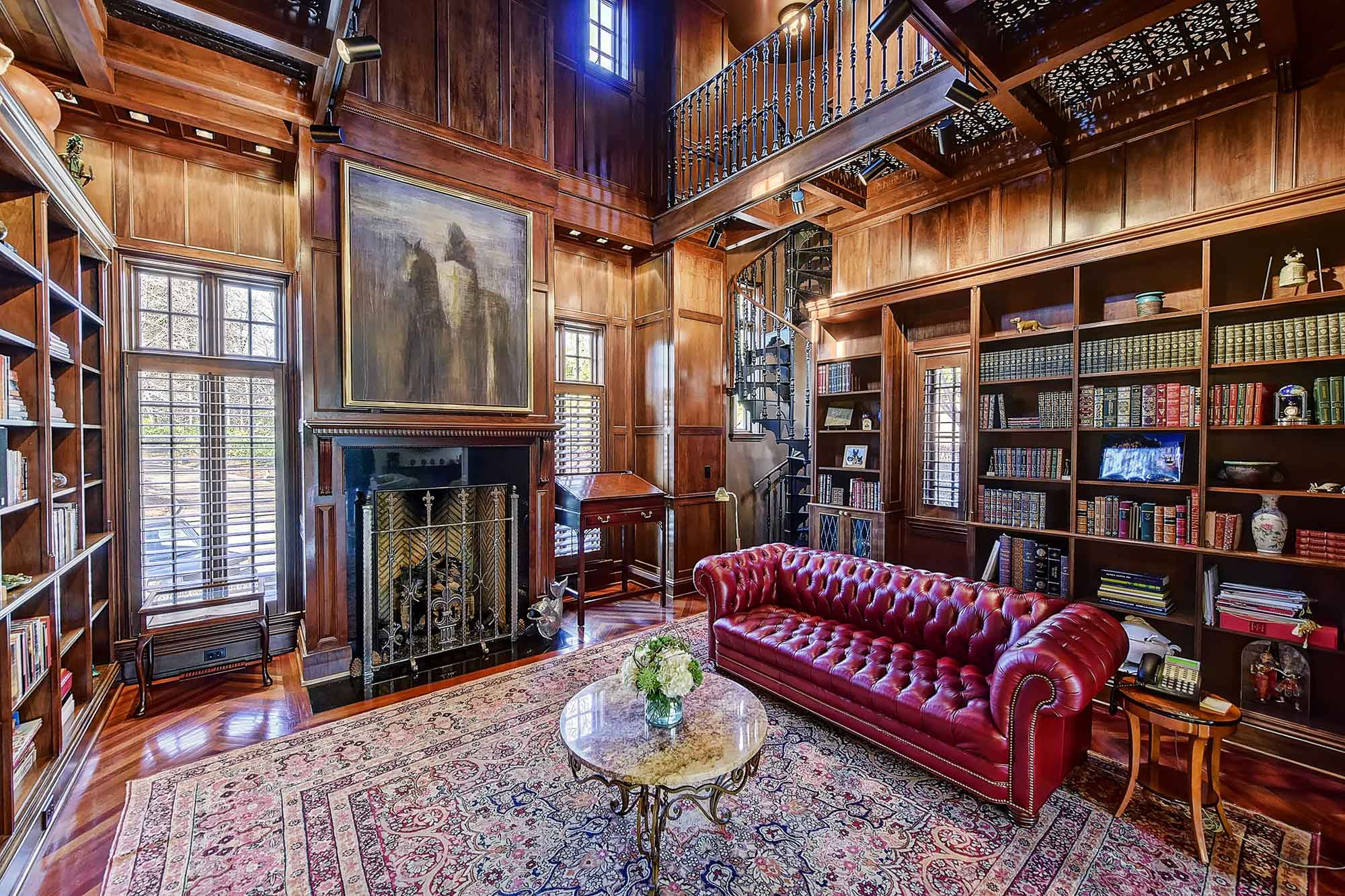 This gated manor house in Pellyn Wood, Charlotte, pays homage to the great estates of England. The library is Tudor in style, with intricate wood paneling, handcrafted bookshelves, and a decorative cast-iron spiral staircase leading up to the mezzanine floor.
