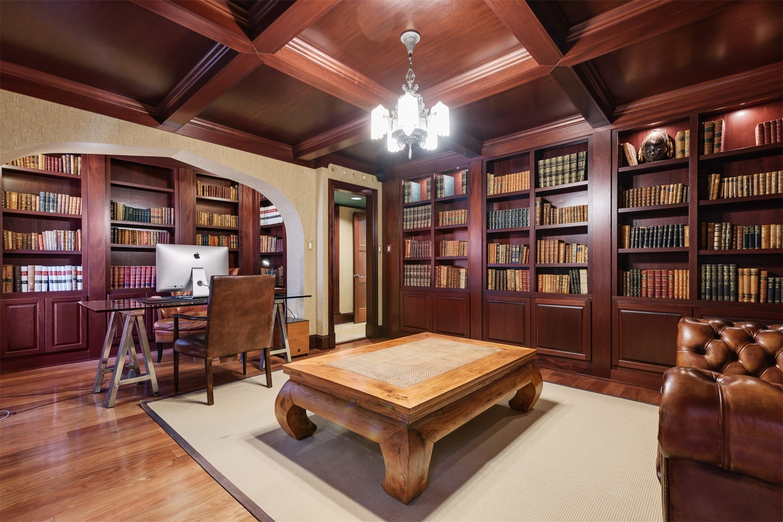 The third bedroom of this elegant residence near Michigan Avenue has been transformed into a delightful private library, complete with coffered ceilings, wood-paneled walls, and floor-to-ceiling mahogany bookshelves.