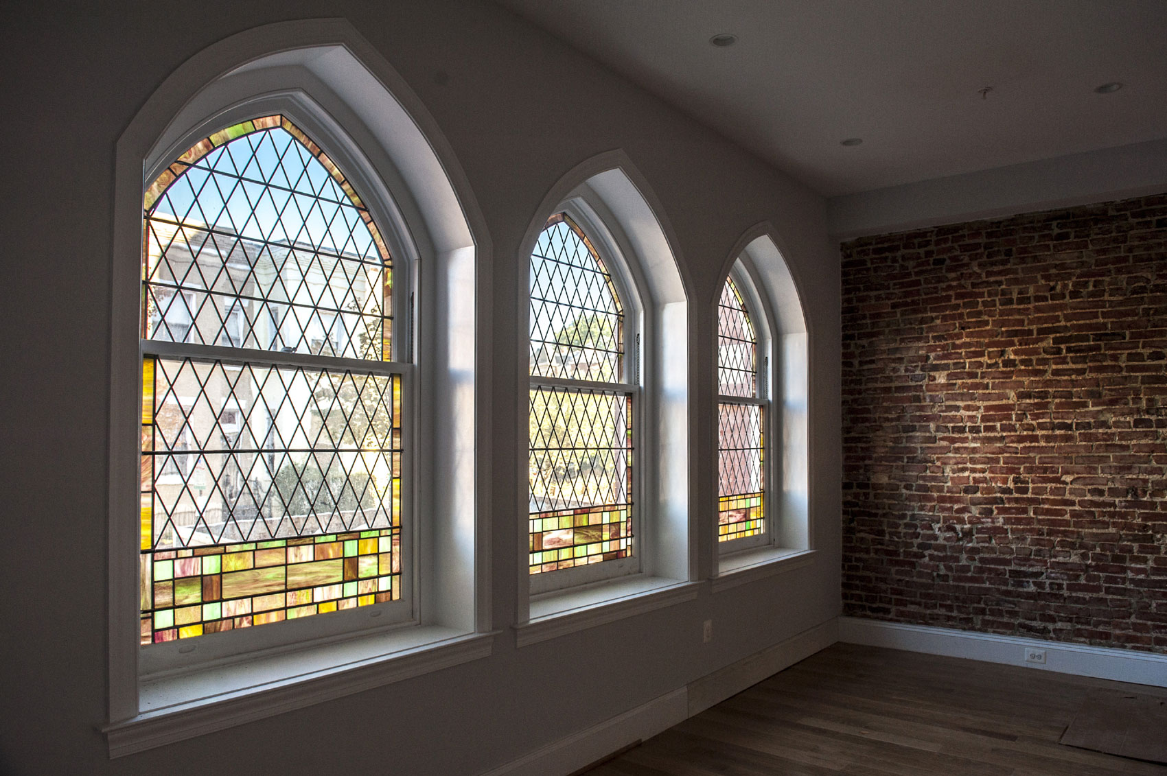 These dramatic Gothic-arched, stained- and leaded-glass windows impart an ethereal aura, creating an unexpected twist on an otherwise chic, modernist aesthetic.