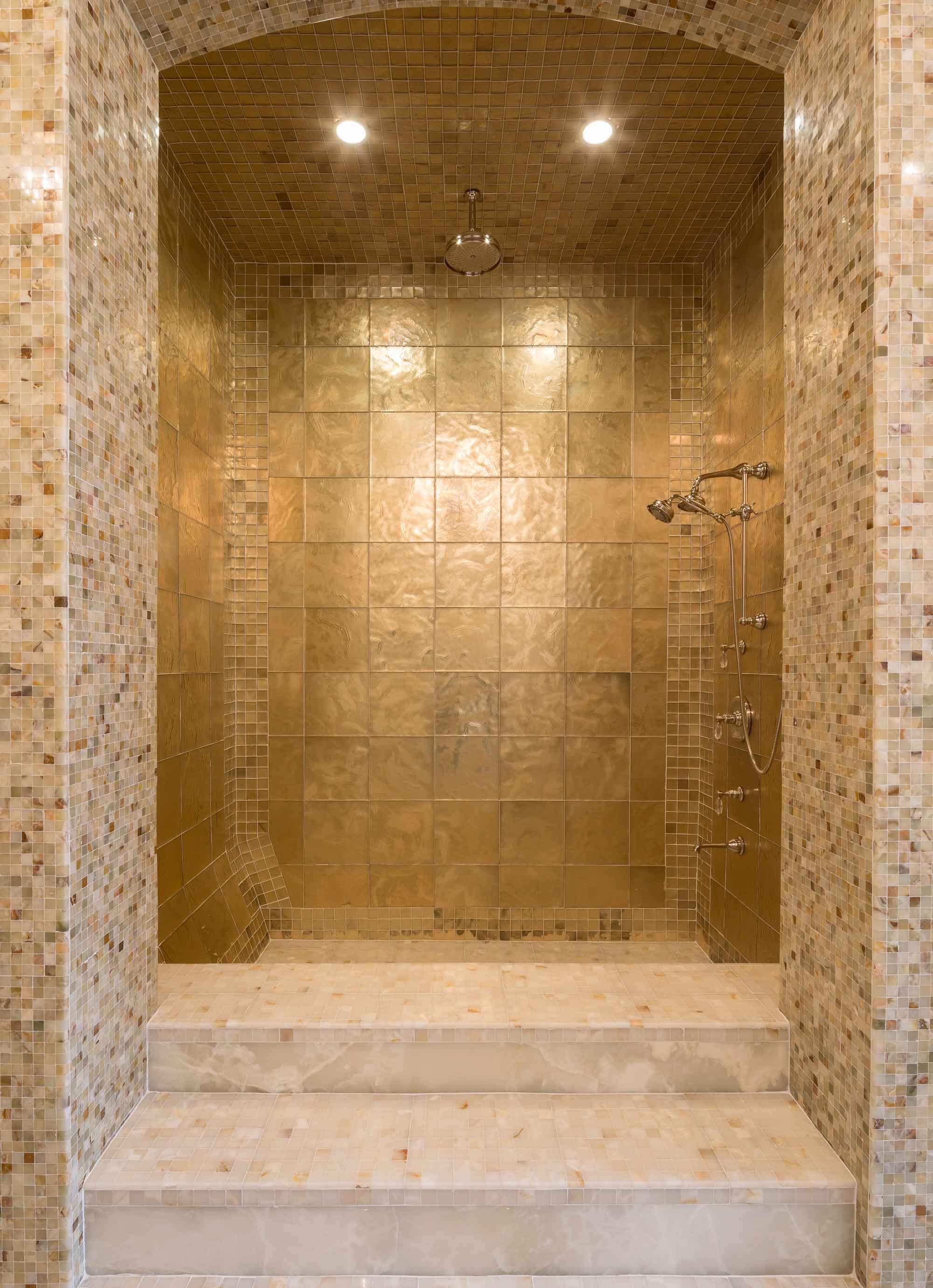 The centerpiece of the master bathroom is a monumental double-height, multi-jet steam shower, finished with beautiful gold marble and mosaic tile.