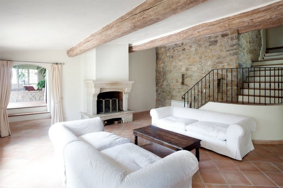 The interior of Mas Plascassier is a study in French country chic with traditional plaster walls, tile floors, wrought-iron details, and exposed beams.