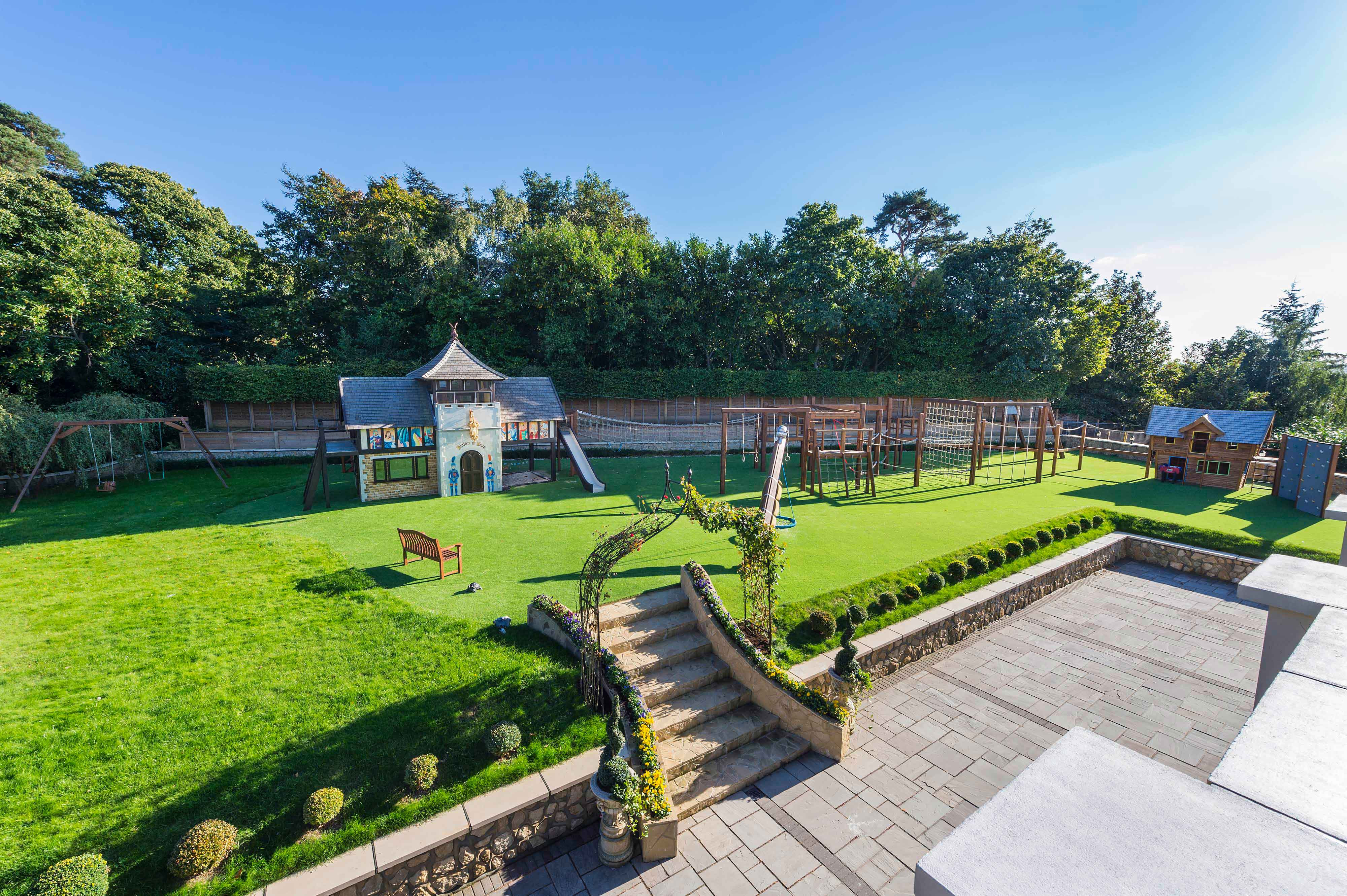 This country estate's child-friendly amenities include a £150,000 playhouse and adventure playground with a slide, zip-wire, climbing wall, and trampoline area; indoor and outdoor pools; and lawns for sports and games.