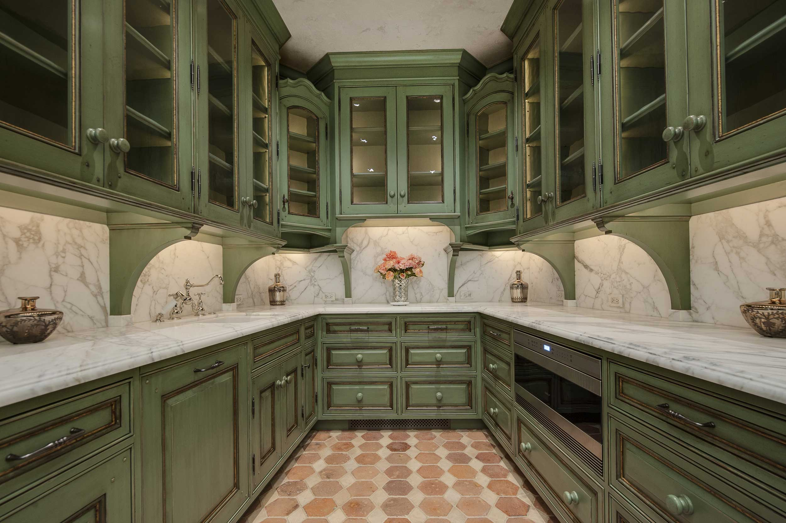 The kitchen also features fine wood details, as well as beautiful marble countertops, and the home's signature color: a perfect shade of green.