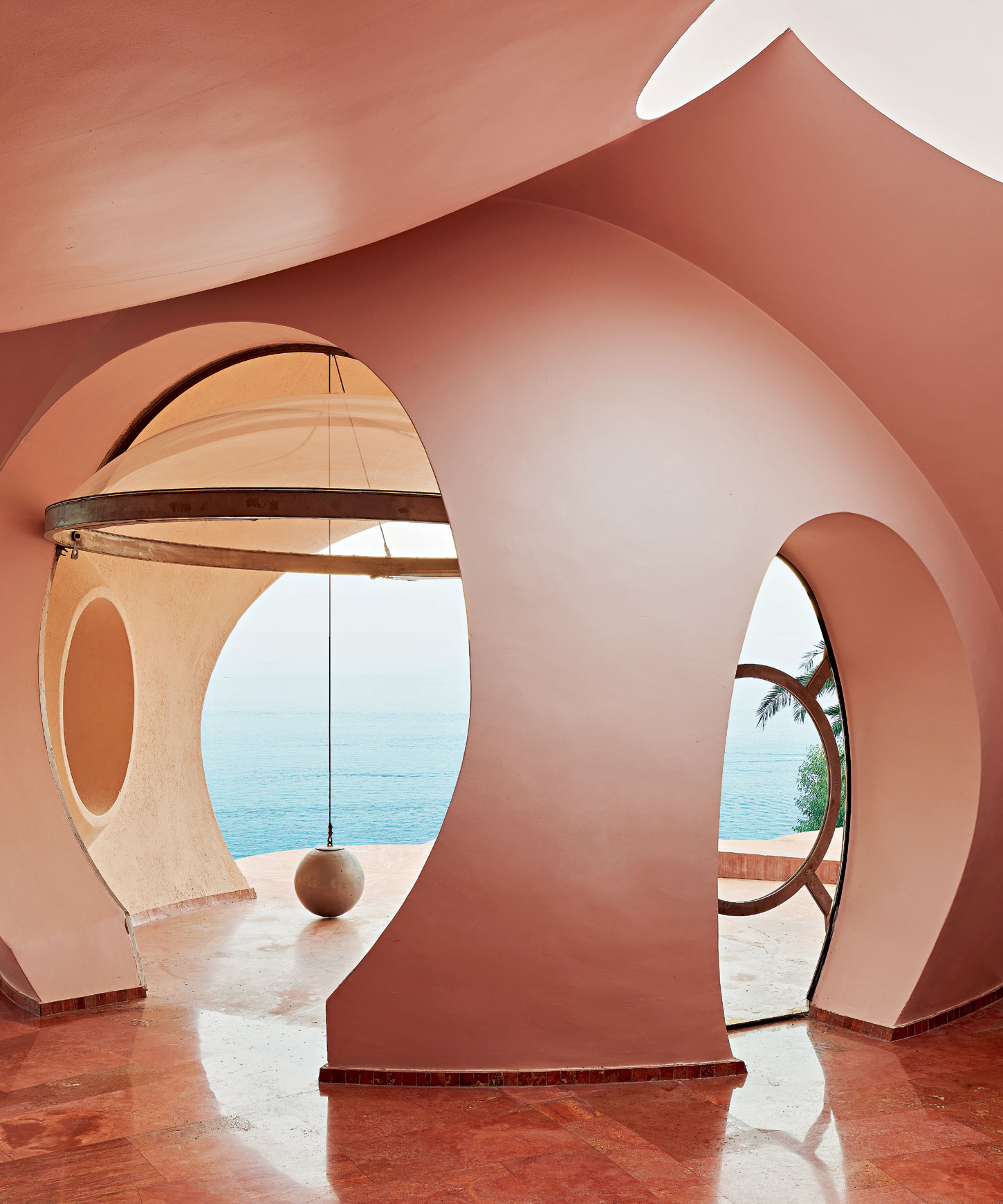 """The clusters of spheres that form the structure of the property come together to create a showstopping interior space—an ideal backdrop for events—while also framing glorious views of the Mediterranean Sea through countless """"portholes."""""""